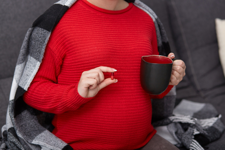 Cropped image of pregnant female takes drug, holds mug with tea, drinks medicine durning pregnancy, needs vitamins, wrapped in plaid, poses at comfortable divan. Medicine and fertility concept