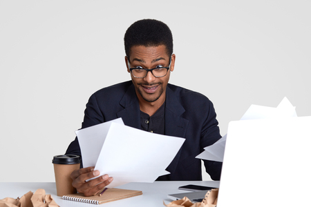 Shocked dark skinned man carries many papers, looks surprisingly through spectacles, wears formal clothes and spectacles, sits at dektop, isolated over white background. People and work concept