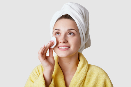 Skin care and beauty treatments concept. Positive young female uses cotton disk for applying cosmetics on face, wears towel and bathrobe, looks joyfully upwards, isolated over white background