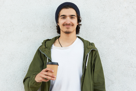 Headshot of pleased hipster guy holds takeaway coffee, dressed in white t shirt and green jacket, enjoys spare time, wears black hat, models over white background, has curly hair. People and drinking