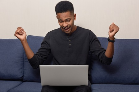 Photo of attractive black man raises hands in fists, exclaims as watches football match online on laptop computer, cheers good result of favourite team, has short curly hair, models indoor on couch