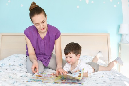 Caring young mother reads magazine with pictures for children to her small son, pose together at bed against cozy interior and blue wall, enjoy domestic atmosphere. Mum and kid. Generation concept