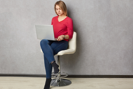 Isolated shot of pretty serious blonde woman focused in laptop computer, sits at white armchair, dressed in red jumper and jeans, poses over grey wall, connected to wireless internet, works freelance Фото со стока