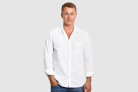 Waist up shot of attractive male entrepreneur wears white shirt and jeans, keeps hand in pocket, isolated over white background. Prosperous young businessman in elegant clothes comes on meeting