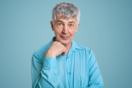 Horizontal shot of mature grey haired Caucasian male pensioner wears elegant shirt, keeps hand under chin, poses for making photo, isolated over blue background. People, age, pension concept Stock Photo