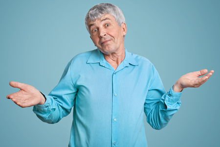 Horizontal shot of hesitant grey haired mature man with wrinkled skin, shruggs shoulders with hesitation, dressed in formal blue shirt in one tone with background. Uncertainty and doubt concept