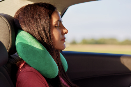 Tired female traveller uses travel pillow, sleeps in car, covers long distance, feels comfort for neck, has long dark hair, closes eyes. People, travelling and journey concept. Sleeping in automobile 版權商用圖片