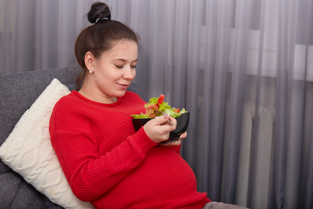 Sideways shot of pleased expectant mother eats fresh vegeterian salad, holds fork, has hair knot, dressed casually, sits at comfortable sofa near window, enjoys healthy eating and lifestyle.
