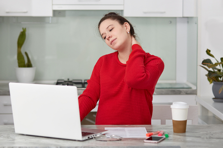 Photo of tired European woman keeps hand on neck, works freelance at laptop computer, wears red sweater, anticipates for baby, poses against kitchen interior, spends time at home on maternity leave Banco de Imagens