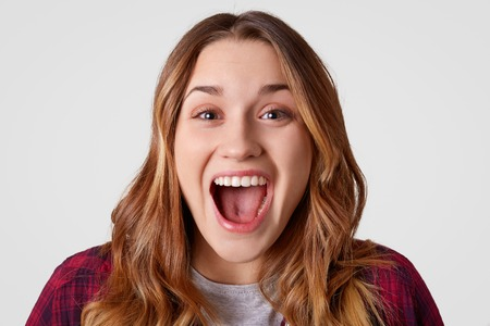 Close up portrait of happy young European woman opens mouth widely, has long wavy hair, being overjoyed, isolated over white background. Stylish lady expresses good emotions. Happiness concept
