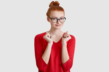 Pleased red haired woman with hair knot, wears transparent glasses, keeps hands over chest, dressed in red jumper, models against white studio wall, expresses joy, anticipates for something. Banco de Imagens