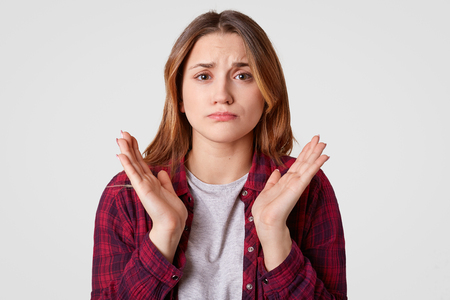 Photo of displeased European woman spreads palms, has pity facial expression, wears casual clothes, isolated over white background, doubts about something. People, disappointment, dissatisfaction