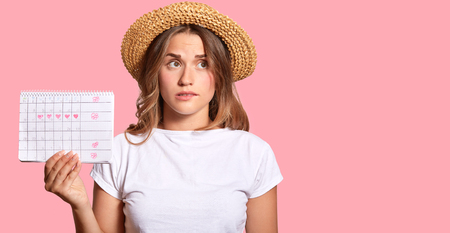 Frustrated Caucasian young woman bites lower lip, dressed in casual white t shirt, holds menstruation calendar, checks days of ovulation, isolated over pink background with free space for your text