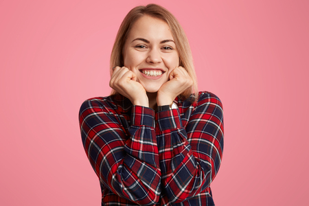 Close up shot of satisfied woman holds chin, smiles broadly, shows white perfect teeth, being in good mood, dressed casually, poses against pink background. Optimistic teenager expresses happiness