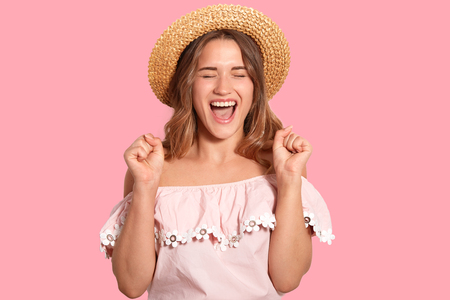 Isolated shot of overjoyed young woman clenches fists with happiness, closes eyes from pleasure, exclaims with triumph, wears fashionable clothes, isolated over pink background. Success concept