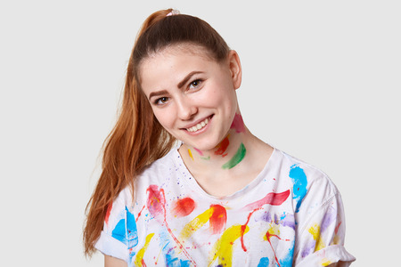Horizontal shot of beautiful female with pony tail, tilts head, has creative occupation, dressed in casual t shirt with watercolour stains, poses against white background. People and inspiration Фото со стока