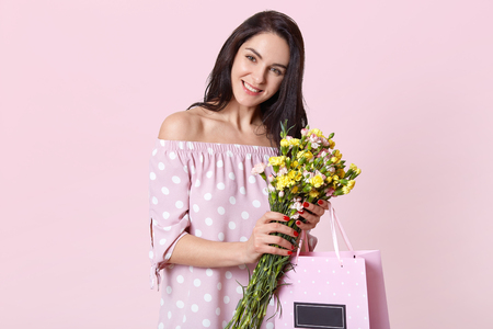 Satisfied good looking woman with dark hair, smiles broadly, holds pretty flowers and gift bag wears summer dress, looks directly at camera with happy expression, models over light pink background Фото со стока