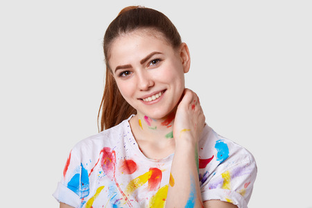Photo of positive European woman keeps hand on neck, smiles broadly, has colourful watercolour stains, has dark hair with pony tail, isolated over white background. Creative person poses indoor