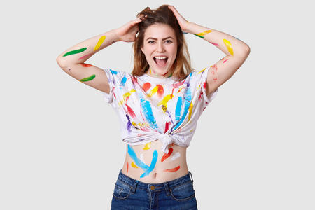 Beautiful happy woman exclaims with joy, keeps hands on head, being dirty after creating masterpiece on canvas, has traces of watercolours on skin and clothes, isolated over white background