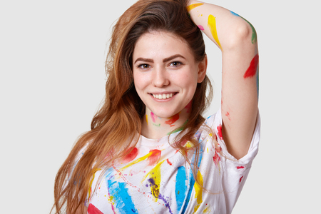 Photo of pleased European female artist, realizes great ideas on canvas, keeps hand behind head, smiles gently, poses against white background, stained with acrylic paints. Art worker indoor Archivio Fotografico
