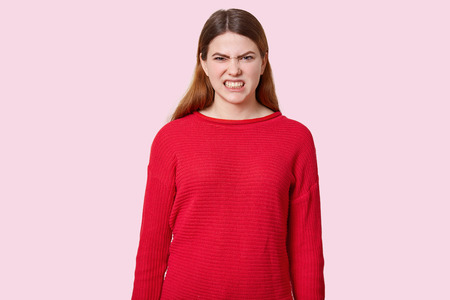 Dissatisfied dark haired woman clenches teeth, frowns face with annoyance, dressed in red sweater, models over rosy background. Grumpy irritated female model sees something negative and bad.