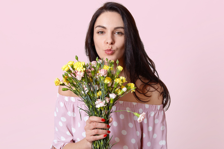 Attractive young female with black hair, keeps lips folded, wants to kiss boyfriend for recieving flowers, wears polka dot dress, isolated over light pink background, has red manicure, minimal makeup
