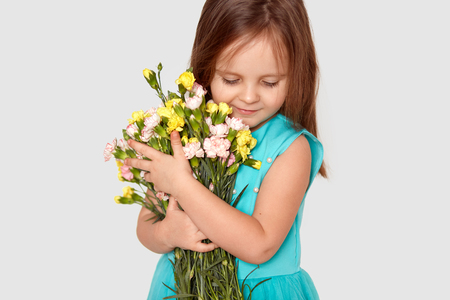 Cropped shot of pleased small Caucasian child with dark hair, focused down, carries beuatiful flowers, dressed in dress, recieves bouquet from father on 8 March, isolated over white background
