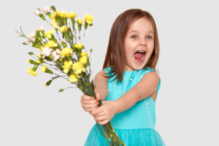 Photo of overjoyed pleased small cute child exclaims happily, dressed in blue dress, holds bouquet of flowers, focused aside, isolated over white background. Childhood and positiveness concept