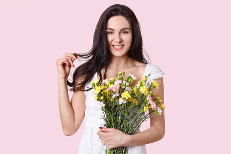 Photo of positive dark haired woman touches hair, smiles gently, has appealing look, holds first spring flowers, has red manicure, dressed in white dress, isolated over rosy background. Beauty concept