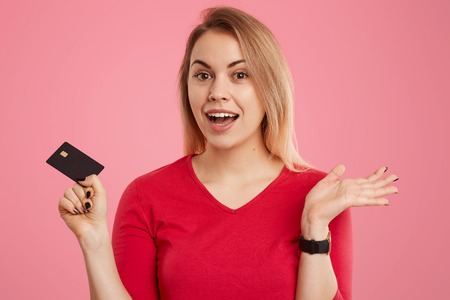 Headshot of positive hesitant light haired European woman dressed in red jumper, holds credit card, has clueless expression, poses over pink background, wants to make payments or transaction.