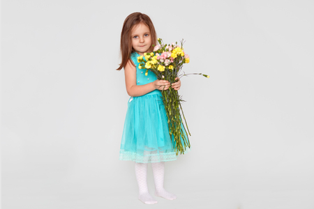 Full length shot of pleasant looking small female kid dressed in blue dress, holds bouquet of flowers, has appealing look, poses over white background, has birthday. Childhood and beauty concept