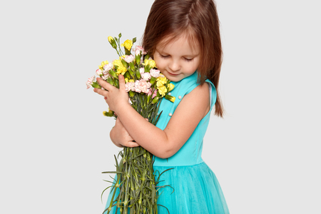 Image of pretty small female child, focused down, dressed in stylish dress, carries bouquet of spring flowers, poses over white background. Adorable girl recieves flowers on 8 March. Children
