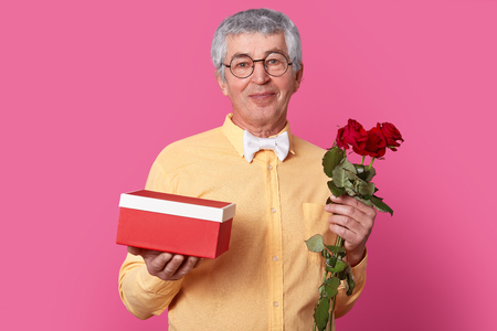 Indoor shot of satisfied elderly gentleman with satisfied expression holds gift box and red roses, dressed in yellow shirt with bowtie, wears spectacles, models over pink background. Its for you