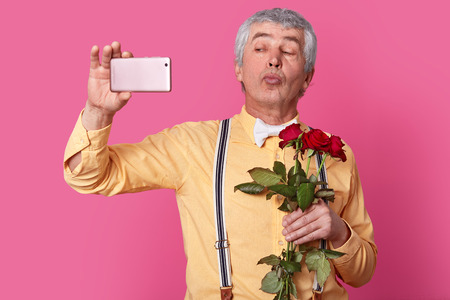 Photo of handsome senior man holds mobilephone in front, makes selfie portrait, pouts lips at camera, wears elegant shirt with suspenders and bowtie, carries red roses, isolated over pink background