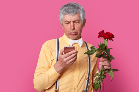 Puzzled indignant senior man cant understand how to send message, holds mobilephone, connected to wireless internet, holds red roses, wears shirt with suspenders, isolated over pink studio wall