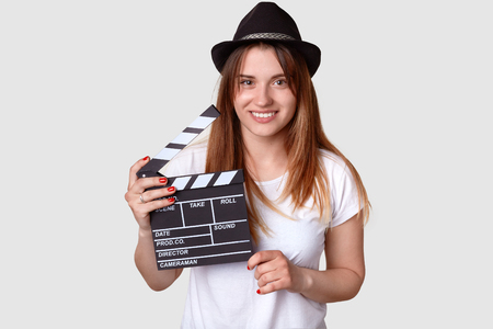 Isolated shot of cheerful woman director involved in sphere of cinematography, holds film clapper, dressed in casual t shirt and hat, isolated over white background. Film making and producing concept 写真素材 - 118457769