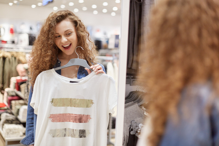 Curly girl with wide smile chooses t shirt in front of large store mirror. These clothes white with stripes in middle of three colors, golden red and silver. You can wear at beach and your home.