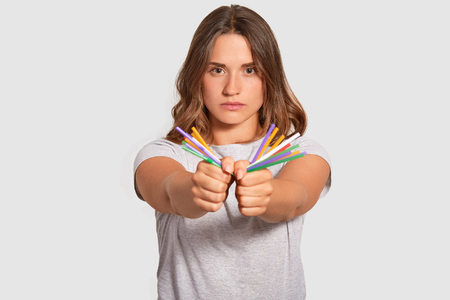 Self confident European woman has serious facial expression, holds plastic straws in hands, looks directly at camera, against of pollution nature by plastic products, isolated over white background