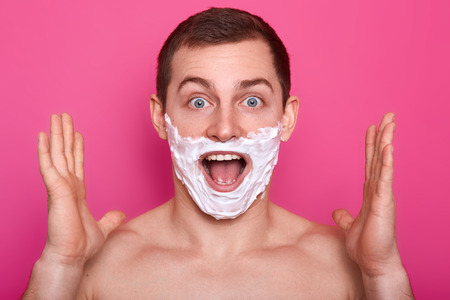 Portrait of excited man with foam on his face. Suprised guy isolated over rose background with shaving cream on cheeks. Male with naked shoulders, clasps hands and looks surprisingly at camera