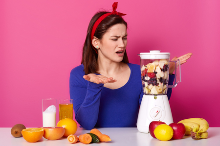 Puzzled woman cannot understand why food processor doesnt work, lgestures with both hands, fails to switch it on, wears red headband and blue jumper, isolated over pink wall. How to make smoothie?