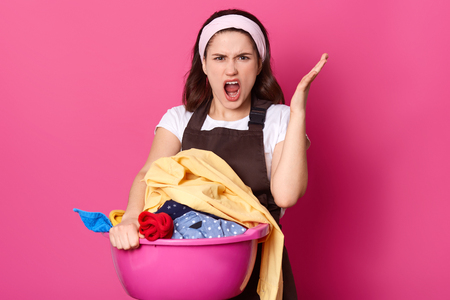 Annoyed beautiful woman raises hand with anger, feels fed up of washing clothes, being overworked, exclaims in dissatisfaction, dressed casually, isolated over pink background. Housework concept Banco de Imagens