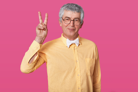 Tempered old senior points two fingers up, wears yellow clothes and white bow tie. Calm smilling pensioner with rounded black spectacles poses against rose wall in studio. People concept. Foto de archivo