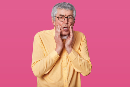 Headshot of stupefied terrified thin man wears yellow shirt, keeps hands on cheeks. Surprised elderly male with glasses against rose wall. Person knows bad news. People and emotions concept. Stockfoto