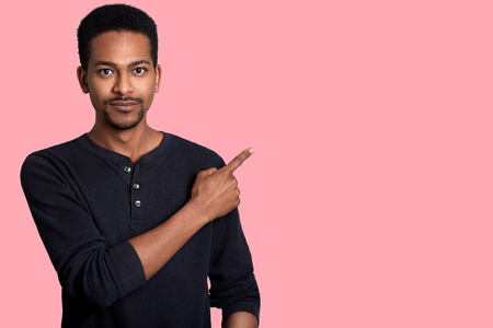 Handsome young african man dresses black shirt, points aside with his right hand. Good looking male shows somethig interesting to his friends. Model poses in studio against pink wall. People concept.