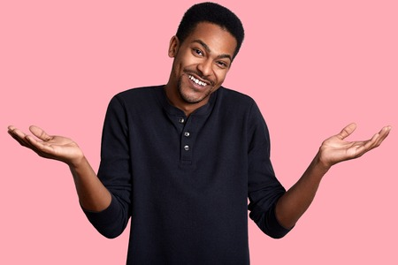 Young dark skinned male in confusion, stands smiling isolated over pink background. Handsome guy wears casual black shirt and makes helpless gesture. Model poses in photo studio. People concept. Stock Photo