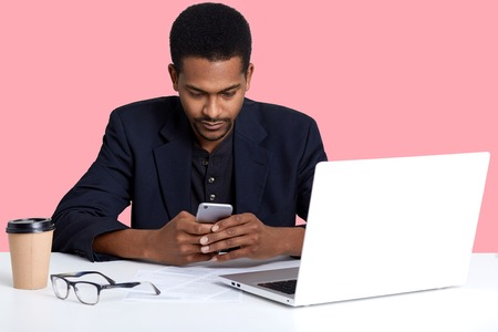 Close up portrait of dark skinned female with smart phone in hands. Handsome black man works online with lap top, decides to have break, checks social net work isolated over pink background.