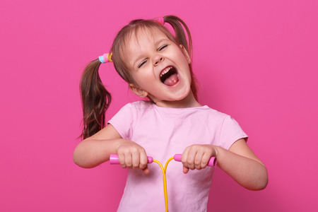 Adorable girl holds skipping rope in hands. Charming female child with opened mouth and narrowed eyes with happy expression.