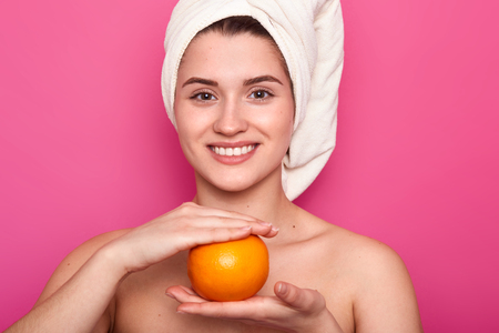 Portrait of attractive cheerful woman with white towel on head, holds orange over pink background. Young smiling female visits spa salon and has rest, takes care of her skin. Natural beauty concept. Imagens
