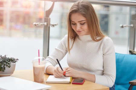 Indoor shot of thoughtful female student prepares for session in cafeteria, writes down some information, drinks fresh cold cocktail, dressed white casual shirt. Students and education concept. Фото со стока
