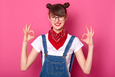 Brunette student with  smiles, makes okay sign with both hands, shows approval. Young girl wears white t shirt, denim overalls with red bandanna on neck. Body language and people concept.
